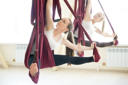 Two young pretty yogi women doing aerial yoga practice in purple hammocks in fitness club. Beautiful models working out in class. Variation of Parivrtta Upavistha Konasana, Revolved Seated Angle Pose