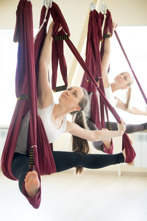 Two young attractive women doing aerial yoga practice in purple hammocks in fitness club. Beautiful models working out in class. Variation of Parivrtta Upavistha Konasana, Revolved Seated Angle Pose Stock Photo