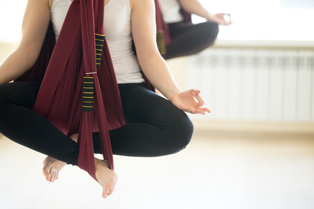 sukhasana: Young beautiful yogi woman doing aerial yoga practice in purple hammock in fitness club. Attractive model working out, sitting in relaxation Sukhasana, Easy Pose, meditating, resting. Close up of hands. Copy space Stock Photo