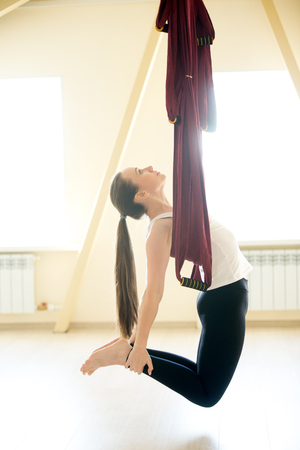 Young beautiful yogi woman doing aerial yoga practice in purple hammock in fitness club. Attractive model working out, bending in ustrasana, camel pose. Full length Stock Photo