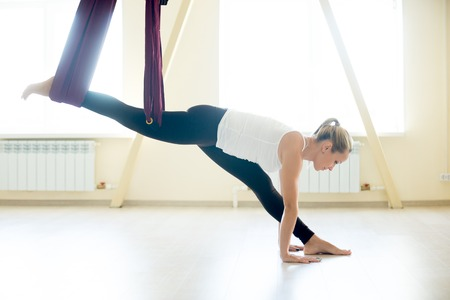 Young attractive yogi woman doing aerial yoga practice in purple hammock in fitness club. Beautiful model working out in class. Variation of monkey god pose, splits, hanumanasana. Full length