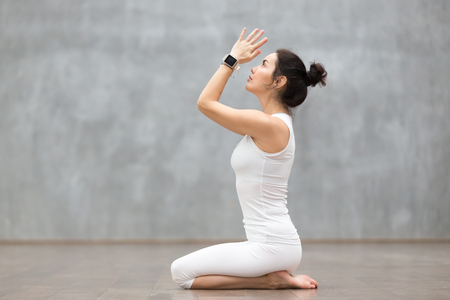 Beautiful young woman wearing sport watch for heart rate and calorie burn control working out against grey wall, doing yoga or pilates exercise. Girl sitting in seiza, vajrasana pose. Full length