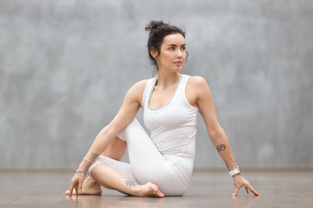 美しい若い女性灰色の壁にワークアウト花のタトゥーとヨガやピラティスの運動を行います。魚、アルダ Matsyendrasana ポーズの半分主に座っている女