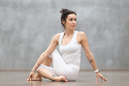 Beautiful young woman with floral tattoo working out against grey wall, doing yoga or pilates exercise. Girl sitting in Half lord of the fishes, Ardha Matsyendrasana pose. Full length