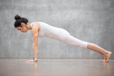 Mooie jonge vrouw, gekleed in witte sportkleding set en smartwatch uit te werken tegen grijze muur, yoga of pilates oefening te doen. Push ups of druk ups, Plank, phalankasana pose. Volledige lengte
