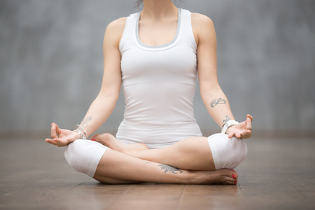 siddhasana: Front view portrait of beautiful young woman with floral tattoos working out against grey wall, resting after doing yoga exercises, sitting in Ardha Padmasana, Lotus pose, relaxing. Close up Stock Photo