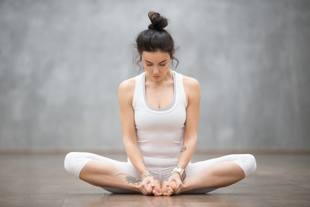 Portrait of beautiful young woman with floral tattoos working out against grey wall, doing yoga or pilates exercise, sitting in baddha konasana, bound angle, cobbler, butterfly pose. Full length shot Stock Photo