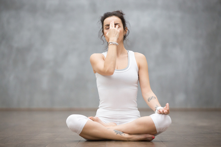 Front view portrait of beautiful young woman wearing white tank top working out against grey wall, resting after doing yoga exercises, using nadi shodhana pranayama technique. Full length Stock Photo