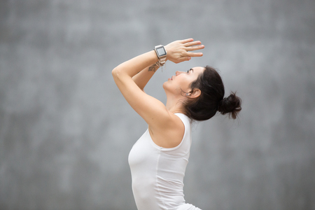 Side view portrait of beautiful young woman wearing sport watch for heart rate and calorie burn control working out against grey wall, doing yoga or pilates exercise. Close up