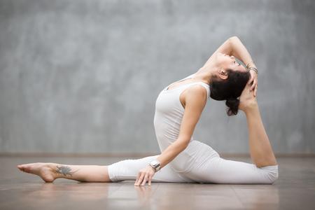 Giovane bella donna che indossa un set di abbigliamento sportivo bianco e uno smartwatch che si allena contro il muro grigio, facendo esercizi di yoga o pilates. Variazione del dio scimmia, spaccature, hanumanasana con piegamento all'indietro. Lunghezza intera
