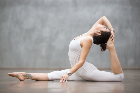 Young pretty woman wearing white sportswear set and smartwatch working out against grey wall, doing yoga or pilates exercise. Variation of monkey god, splits, hanumanasana with backbend. Full length