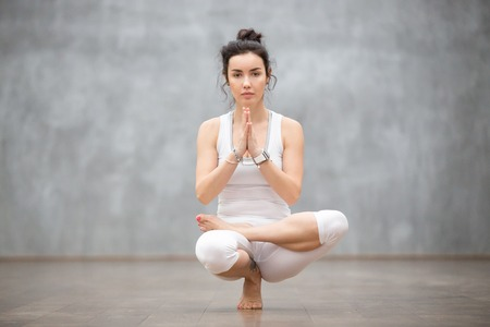 Young calm pretty woman wearing white sportswear working out against grey wall, doing yoga or pilates exercise. Sitting in squat position, Half Lotus Toe Balance, variation of Utkatasana. Full length Imagens
