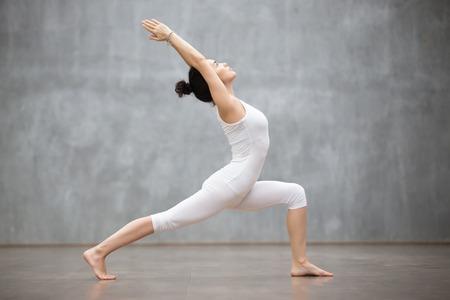 Vista lateral retrato de la hermosa mujer joven con camiseta blanca que se resuelve contra la pared gris, hacer yoga o ejercicios de Pilates. De pie en una pose de Guerrero, Virabhadrasana. Longitud total Foto de archivo