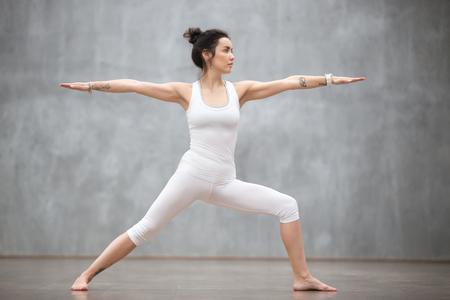 Ritratto di vista laterale di bella giovane donna che indossa canotta bianca che si allena contro il muro grigio, facendo esercizio di yoga o pilates. In piedi nella posa del guerriero due, Virabhadrasana. Lunghezza intera