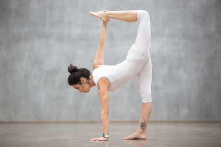 Profile portrait of beautiful young woman wearing white tank top working out against grey wall, doing yoga or pilates exercise. Standing in variation of Half Moon pose, Ardha Chandrasana. Full length