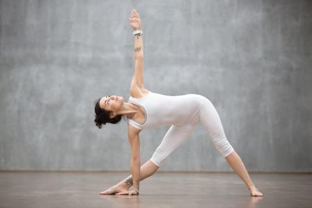 요가 또는 필 라텍스 운동을 하 고 회색 벽에 밖으로 작동하는 흰색 운동복을 입고 아름 다운 젊은 여자의 프로필 초상화. Utthita Trikonasana에 서서, 연장