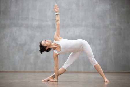 Profielportret van mooie jonge vrouw die witte sportkleding dragen die tegen grijze muur uitwerken, die yoga of pilates oefening doen. Staand in Utthita Trikonasana, uitgebreide driehoekshouding. Volledige lengte