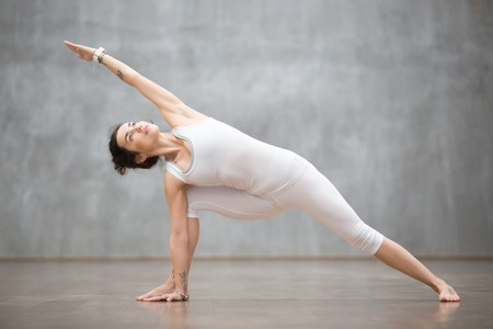 side angle pose: Portrait of beautiful young woman wearing white sportswear working out against grey wall, doing yoga or pilates exercise. Standing in Utthita parsvakonasana, extended side angle pose. Full length Stock Photo