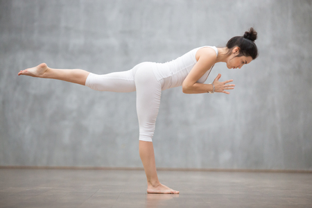 Side view portrait of beautiful young woman wearing white tank top working out against grey wall, doing yoga or pilates exercise. Standing in Warrior three pose, Virabhadrasana 3. Full length Imagens