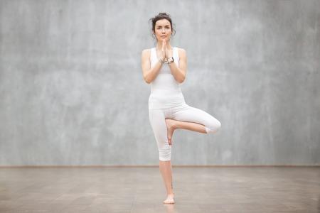 Portret van mooie jonge vrouw die witte sportkleding draagt die tegen grijze muur uitoefent, yoga of pilates oefening doet. Staan in Vrksasana, Boom vormen. Volledige lengte