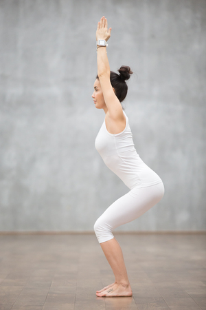 Side view portrait of beautiful young woman wearing white sportswear working out against grey wall, doing yoga or pilates exercise. Standing in Chair, Utkatasana pose. Full length Stock Photo