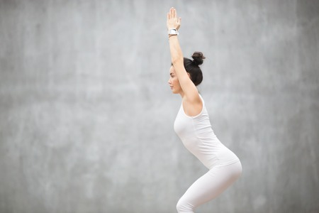 Side view portrait of beautiful young woman wearing white sportswear working out against grey wall, doing yoga or pilates exercise. Standing in Chair, Utkatasana pose. Copy space