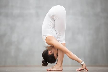 ヨガやピラティスの運動をしている灰色の壁に対して作業を彼女の足の意味野生ハローキティの刺青の美しい若い女性の肖像画。Uttanasana、ベンド前