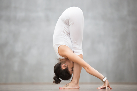 Portret van mooie jonge vrouw met tatoeage op haar voet die Wild kat betekenen die tegen grijze muur uitwerken, die yoga of pilates oefening doen. Uttanasana, staat voorovergebogen. Foto van volledige lengte