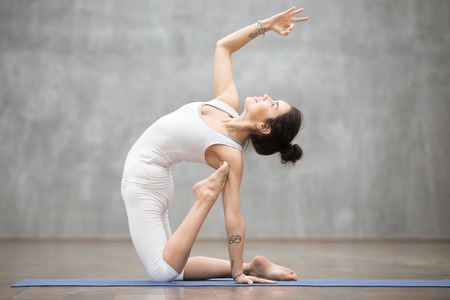 Side view portrait of beautiful slim young woman with tattoo working out in fitness center against grey background, doing yoga or pilates exercise. Variation of ustrasana, camel pose. Full length