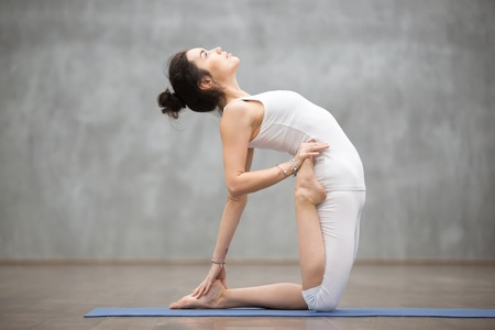 ushtrasana: Side view portrait of beautiful young woman wearing white sportswear working out in fitness center against grey wall, doing yoga or pilates exercise. Variation of ustrasana, camel pose. Full length