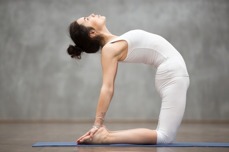 Side view portrait of beautiful young woman wearing white sportswear working out in fitness center against grey wall, doing yoga or pilates exercise. Classical ustrasana, camel pose. Full length