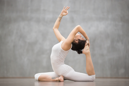 Side view portrait of attractive young woman with beautiful tattoo working out in fitness club or at home, doing yoga or pilates exercise. One Legged King Pigeon pose, Eka Pada Rajakapotasana 写真素材