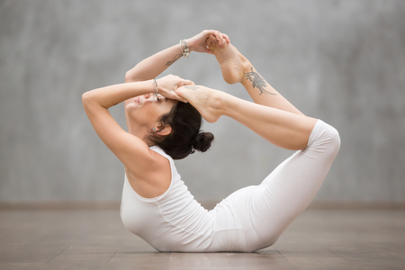 Side view portrait of attractive young woman with tattoo on her foot meaning Wild kitty working out in fitness club or at home, doing yoga or pilates exercise. Variation of Dhanurasana, Bow pose