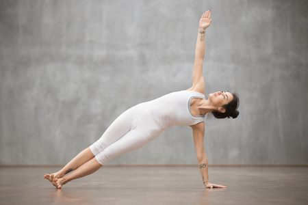 Side view portrait of attractive young woman with beautiful tattoo working out in fitness club or at home against grey wall, doing yoga, pilates exercise. Side Plank, Vasisthasana pose. Full length