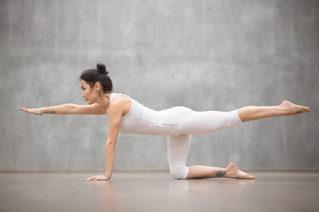 Side view portrait of attractive young woman with beautiful tattoo working out against grey wall, doing yoga, pilates balancing exercise. Bird dog, chakravakasana pose. Full length
