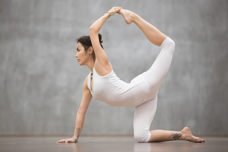 Side view portrait of attractive young woman with beautiful tattoo working out against grey wall, doing yoga, pilates balancing exercise. Sunbird, chakravakasana pose. Full length Stock Photo