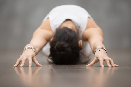 Attractive young woman wearing white sportswear working out against grey wall, doing yoga, pilates exercise. Child Pose, Balasana pose. Focus on hands