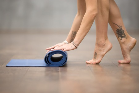 Attractive young woman with beautiful tattoo on her foot meaning Wild kitty folding blue yoga or fitness mat after working out at home or in club. Close up of foot. Healthy life concept