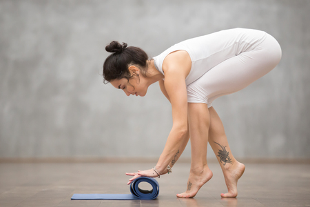 unfolding: Attractive smiling young woman wearing white sportswear with beautiful tattoos folding blue yoga or fitness mat after working out at home or in club. Full length photo. Healthy life concept