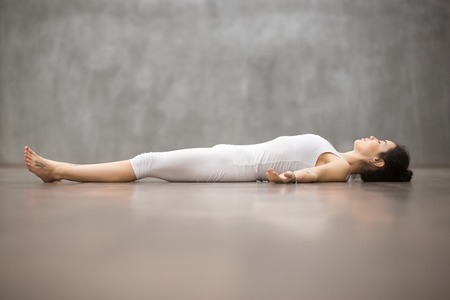 Side view portrait of beautiful young woman working out against grey wall, resting after doing yoga exercises, lying in Savasana Corpse or Dead Body Posture , relaxing. Full length