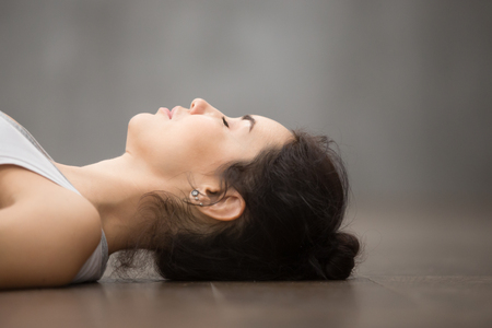 Side view portrait of beautiful young woman working out against grey wall, resting after doing yoga exercises, lying in Shavasana Corpse or Dead Body Posture , relaxing. Face close up Stock Photo