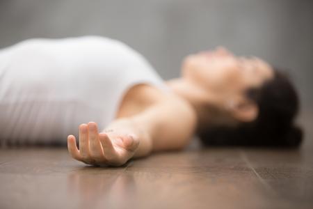 Mooie jonge vrouw die op houten vloer werkt, rustend na het doen van yoga oefeningen, liggen in Shavasana Corpse of Dead Body Posture, ontspannend. Close-up, focus op de hand Stockfoto