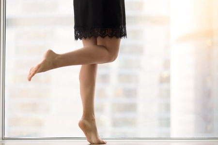 footcare: Female bare legs, staying on tiptoe, healthy legs, smooth skin, helping mind and body relax and rejuvenate after work, taking dancing classes, exercising at morning at window with city view. Close up