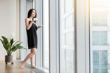 Plein longueur de jeune femme debout près d'une fenêtre en appréciant le café, en regardant la ville après le réveil au matin, vêtu de noir nightwear de soie, se reposant de l'entreprise, en attendant le beau temps