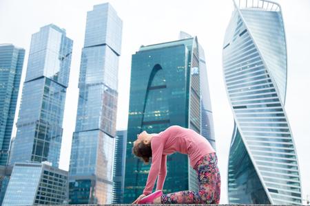 요가 연습, 젊은 매력적인 여자 낙타 운동, Ustrasana 포즈, 핑크 운동복, 야외 전체 길이, 현대 도시 마천루 배경 입고 작업 앉아