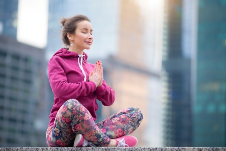 Young happy woman with closed eyes practicing yoga, sitting in Easy Seat exercise, Sukhasana pose, meditation session, working out wearing pink sportswear, outdoor full length, urban city background