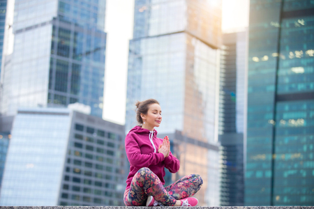 Young attractive woman practicing yoga, sitting in Easy Seat exercise, Sukhasana pose, working out wearing pink sportswear, outdoor, modern skyscraper background, her eyes closed, focused. Copy space