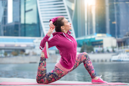 Young attractive woman practicing yoga, standing in Horse rider exercise, variation of anjaneyasana pose, working out wearing pink sportswear, outdoor full length, skyscraper and river background