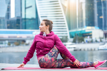 Young attractive woman practicing yoga, sitting in Half lord of the fishes exercise, Ardha Matsyendrasana pose, working out wearing pink sportswear, outdoor full length, modern urban city background Stock Photo