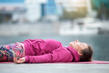 Young attractive woman practicing yoga, lying in Dead Body exercise, Savasana, Corpse pose, relaxing, refreshing after sport, wearing nice pink sportswear, outdoor city, river background, close up Stock Photo